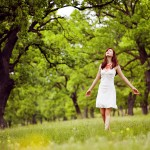 beautiful woman in white walking through the green forest in sum